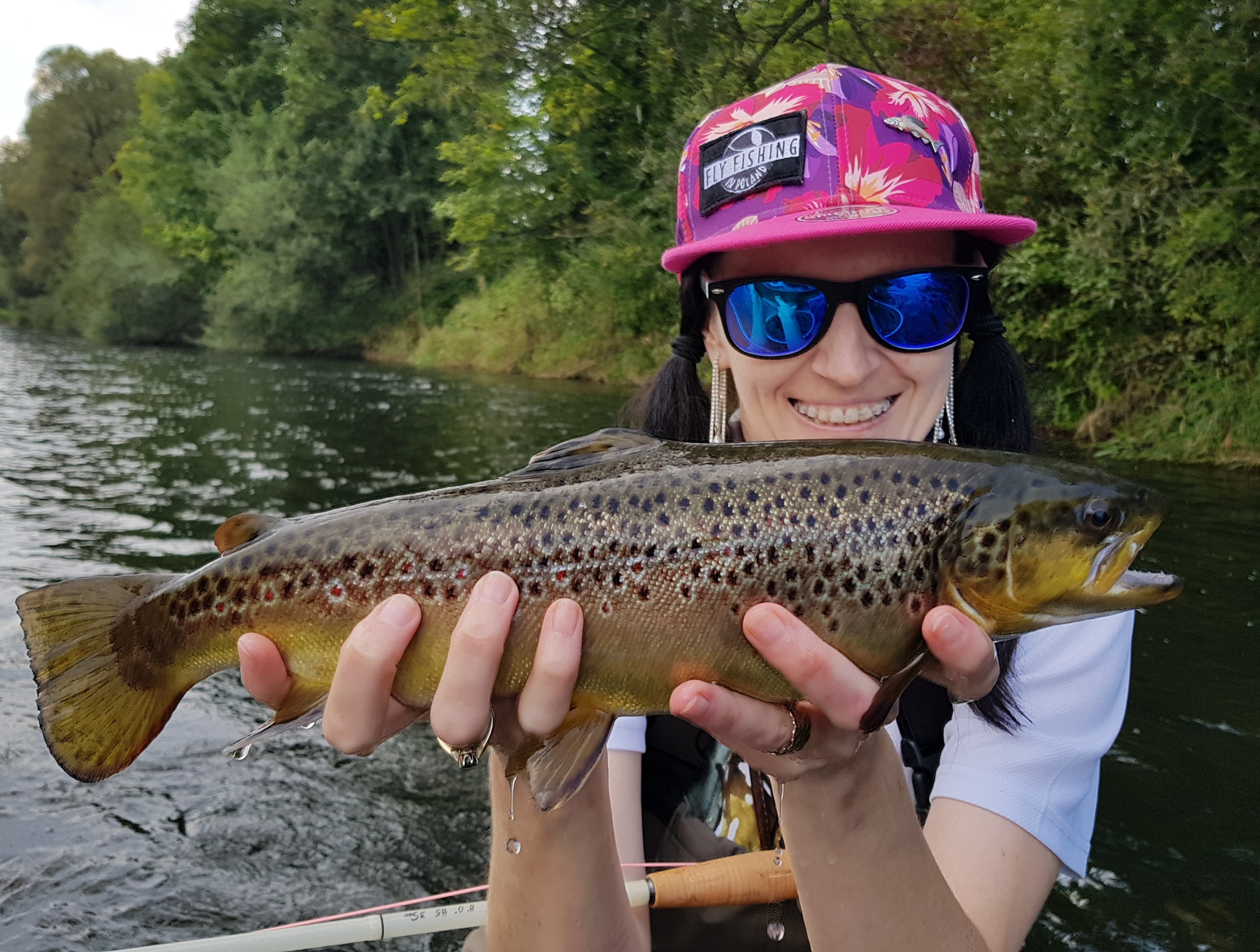 Happy angler with Brown Trout, girl fly fishing,